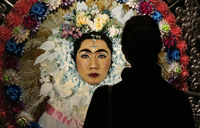 """A visitor looks at the art work """"An Dialogue with Frida Kahlo Flower Wreath and Tears. Flower Tondo"""" during press preview of the exhibition of Japan artist Yasumasa Morimura """"The history of the self-portrait solo"""" in The Pushkin State Museum of Fine Arts in Moscow, Russia, 30 January 2017. The exhibition shows more then 80 pieces from the collection of The National Museum of Art in Osaka, Hara Museum of Contemporary Art in Tokyo, The National Museum of Modern Art in Kyoto, and from the collection of Yasumasa Morimura. (Photo y Yuri Kochetkov/EPA)"""