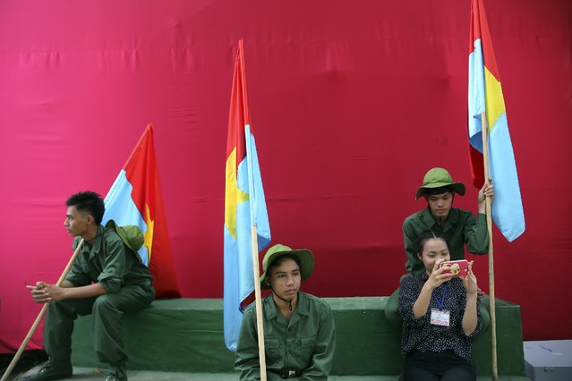 An artist takes selfie photo with others who are in military uniform and hold Vietcong flags on the backstage during a parade celebrating the 40th anniversary of the end of the Vietnam War which is also remembered as the fall of Saigon, in Ho Chi Minh City, Vietnam, Thursday, April 30, 2015. (Photo by Na Son Nguyen/AP Photo)