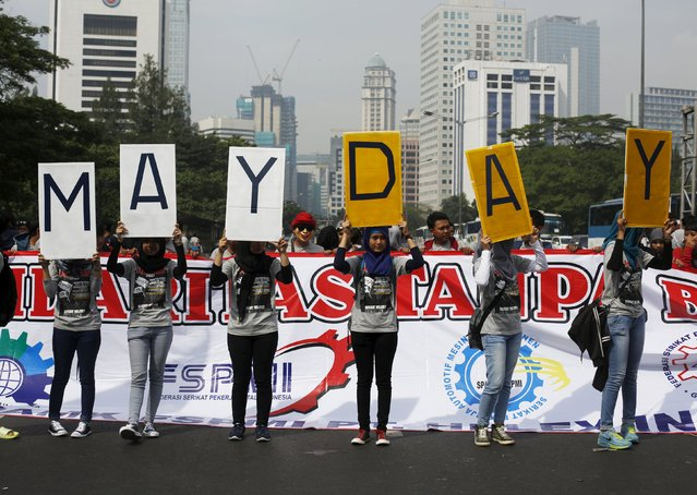 People hold placards during a May Day rally in Jakarta, Indonesia, May 1, 2015. Thousands of workers urged the government to raise minimum wages and improve working condition, according to local media. (Photo by Reuters/Beawiharta)
