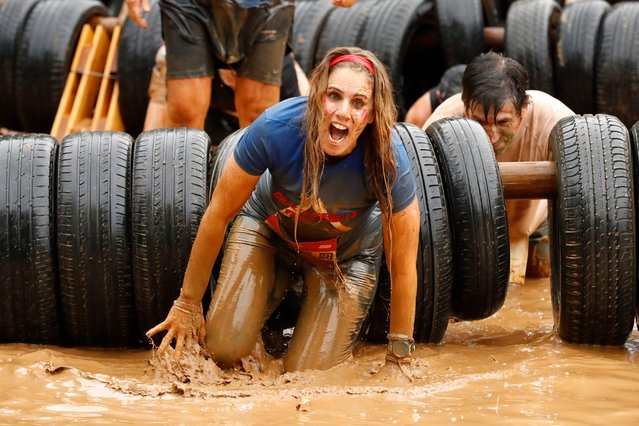 "Participants creep under tires in a 10km obstacle course during the ""Run Mud"" race, on March 29, 2019 in the Israeli mediterranean coastal city of Tel Aviv. (Photo by Jack Guez/AFP Photo)"