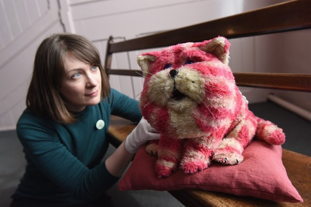"""Curator Alice Sage holds up the original Bagpuss during a photocall for the Bagpuss And The Clangers Retrospective Of Smallfilms at the V&A Museum Of Childhood on March 17, 2016 in London, England. Bagpuss is a British children's television series, made by Peter Firmin and Oliver Postgate. The series of 13 episodes was first broadcast from 12 February 1974 to 7 May 1974 through their company Smallfilms. The title character was """"a saggy, old cloth cat, baggy, and a bit loose at the seams"""". (Photo by Gareth Cattermole/Getty Images)"""