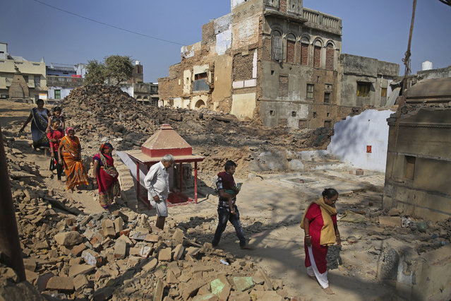 In this March 19, 2019 photo, Hindu devotees walk barefoot through debris of demolished houses to reach river Ganges at the site of a proposed grand promenade connecting the sacred Ganges river with a centuries-old temple dedicated to Lord Shiva, in Varanasi, India. The $115 million promenade is just one of a number of India Prime Minister Narendra Modi's religious glamor projects, aimed squarely at pleasing his Hindu nationalist base ahead of elections that start this month. (Photo by Altaf Qadri/AP Photo)