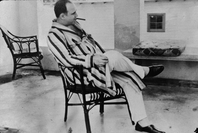 "American gangster Al Capone (""Scarface"") (1899 – 1947) relaxes in his vacation home, Miami, Florida, 1930. Capone smokes a cigar and wears a striped dressing gown and slippers. (Photo by New York Times/Getty Images)"