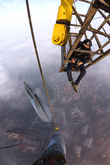 Vadim Makhorov sitting in a cage above the Shanghai tower, China. (Photo by Vitaly Raskalov/Caters News Agency)