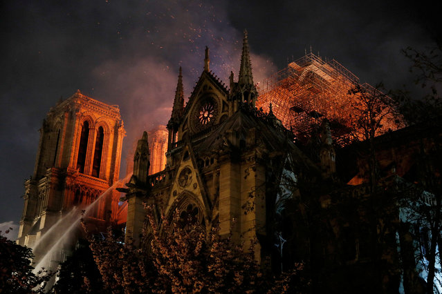 Sparks fill the air as Paris Fire brigade members spray water to extinguish flames as the Notre Dame Cathedral burns in Paris, France, April 15, 2019. (Photo by Philippe Wojazer/Reuters)
