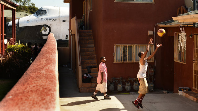 Traymond Harris, left, and Ryan Hudge play basketball as the shuttle Endeavour passes by on Crenshaw Avenue on October 13, 2012 in Inglewood, California. (Photo by Wally Skalij/Getty Images)