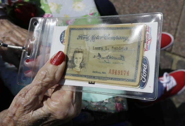 """Former Rosie, Laura Eglinsdoerfer holds her Ford Motor Co., identification card, Tuesday, March 22, 2016 in Washington. Seven decades after their """"we can do it"""" attitude proved invaluable to the Allied victory in World War II, some """"Rosie the Riveters"""" were honored Tuesday with a visit to Washington. (Photo by Carlos Osorio/AP Photo)"""