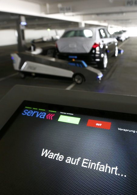 "Automated guided vehicle robot ""Ray"" lifts up an Audi car during a pilot project at the parking area of the Audi plant in Ingolstadt, Germany, May 13, 2015. Words at working station read ""Wait for bringing in"". (Photo by Michaela Rehle/Reuters)"