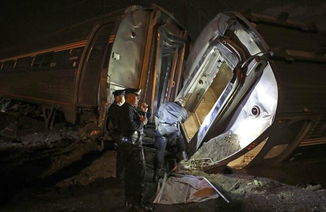 Emergency personnel work the scene of a train wreck, Tuesday, May 12, 2015, in Philadelphia. An Amtrak train headed to New York City derailed and crashed in Philadelphia. (Photo by Joseph Kaczmarek/AP Photo)