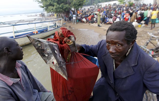 A Burundian refugee carries his belongings as he boards a boat on the shores of Lake Tanganyika in Kagunga village in Kigoma region in western Tanzania to Kigoma township, May 17, 2015. (Photo by Thomas Mukoya/Reuters)
