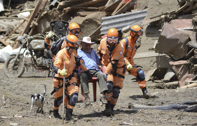 Rescue workers aid a victim of an avalanche in Salgar, in Colombia's northwestern state of Antioquia, Tuesday, May 19, 2015. The avalanche of mud and debris roared through the mountain town before dawn Monday, taking away homes and bridges. Authorities said the death toll, which had risen to 62, was likely to grow throughout the day as an undetermined number of people remain missing. (Photo by Luis Benavides/AP Photo)
