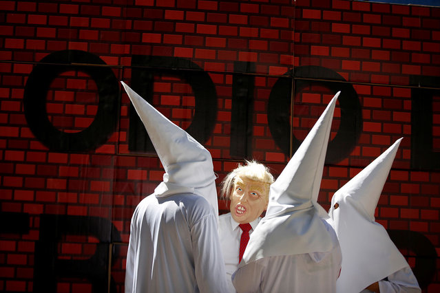 "Actors impersonating U.S. President Donald Trump and members of the Ku Klux Klan stage a performance on behalf of a local Mexican political party during a protest against Trump, in Mexico City, Mexico February 20, 2017. The writing on the mock wall reads ""Hatred"". (Photo by Jose Luis Gonzalez/Reuters)"