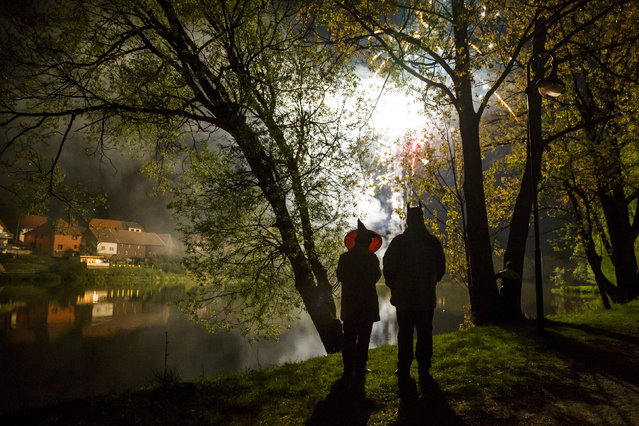 People stand by a lake as they watch fireworks explode over a Walpurgisnacht pagan festival in the town of Stiege, in the Harz mountain region, April 30, 2014. Legend has it that on Walpurgisnacht or May Eve, witches fly their broomsticks to meet the devil at the summit of the Brocken Mountain in Harz. In towns and villages scattered throughout the mountain region, locals make bonfires, dress in devil or witches costumes and dance into the new month of May. Picture taken April 30, 2014. (Photo by Thomas Peter/Reuters)