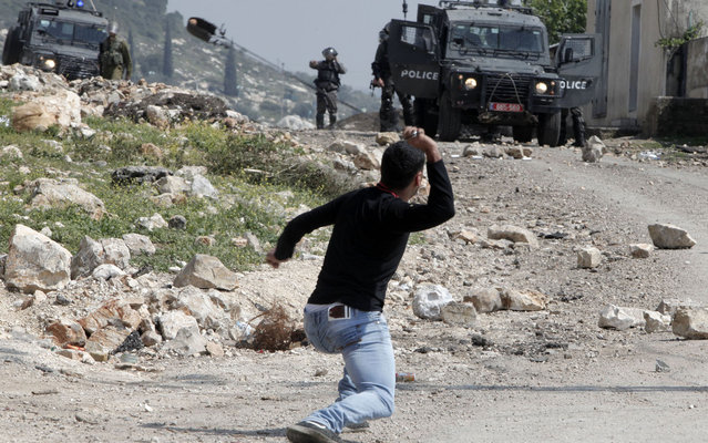 A Palestinian man uses a slingshot to throw stones during clashes with Israeli security forces following a weekly protest against the expropriation of Palestinian land by Israel in the village of Kfar Qaddum, near Nablus, in the occupied West Bank on March 21, 2014. (Photo by Jaafar Ashtiyeh/AFP Photo)