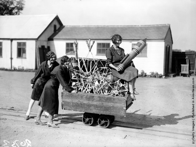 1929: Three women pushing along a truck-load of fireworks in Paris