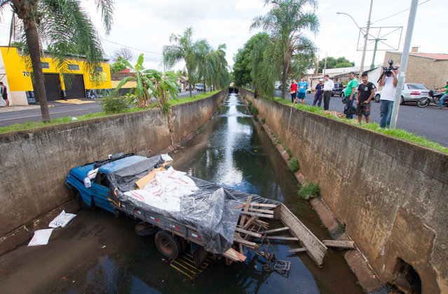 A truck falls into stream in Ribeirão Preto, São Paulo, on March 24, 2014. (Photo by Alfredo Risk/Futura Press/Estadão Conteúdo)