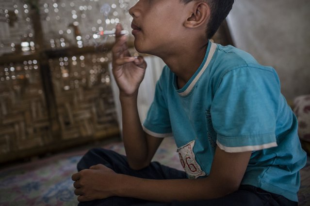Bilal (13), smokes at a kiosk on March 6, 2017 in Yogyakarta, Indonesia. (Photo by Ulet Ifansasti/Getty Images)