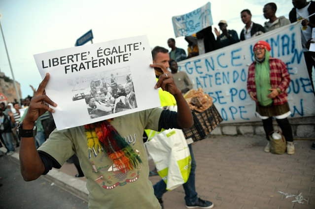 In this picture taken Monday, June 15, 2015, a migrant shows a poster bearing the national motto of France 'Liberty, Equality, Fraternity' in Ventimiglia, at the Italian-French border. French border police blocked border crossings last week, citing the influx of migrants, and about 200 would-be refugees who have been camping out for days in hopes of continuing their journeys farther north have refused to leave the rocks of Ventimiglia, just a few kilometers from the swank resorts of Nice and Saint-Jean-Cap-Ferrat on the French Riviera. (Luca Zennaro/ANSA via AP)