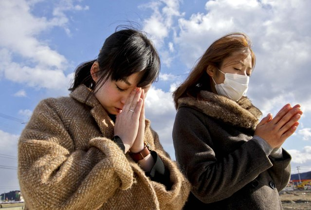 People offer prayers during a moment of silence in front of what is left of a disaster control center in an area devastated by the March 11, 2011 earthquake and tsunami in Minamisanriku, Miyagi Prefecture. Japan marked the second anniversary of the devastating disasters that left nearly 19,000 people dead or missing. (Photo by Shizuo Kambayashi/Associated Press)