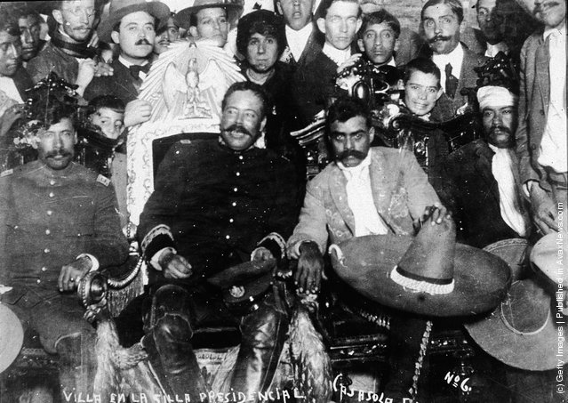 Mexican revolutionary leaders Emiliano Zapata (C, Left) (1879 - 1919) and Pancho Villa (1878 - 1923) (C, Right) sit in front of a group of soldiers, January 2, 1915