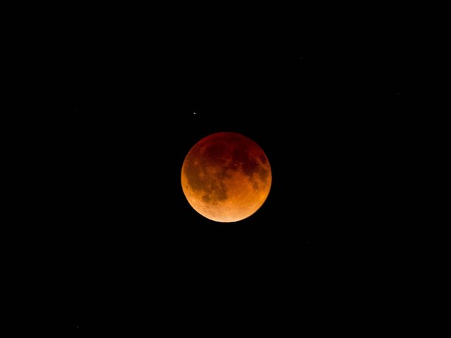 A total lunar eclipse in the sky over the Mexican city of Guadalajara. (Photo by Hector Guerrero/AFP Photo)