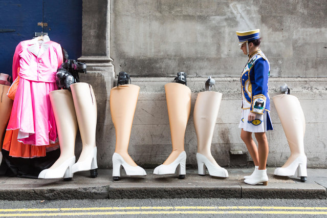 A member of the Mayobridge band from County Down walks past pairs of leg-shaped stilts ahead of the St Patrick's Day parade in London, UK on March 17, 2017. (Photo by Vibrant Pictures/Alamy Live News)