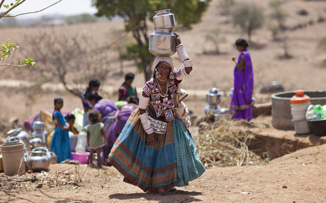 An indigenous Indian woman in her traditional attire walks after collecting water from public tap on the eve of World Water Day, outskirts of Hyderabad, India, Tuesday, March 21, 2017. There is no direct supply of potable water at homes in most of the poor neighborhoods in the country and people have to depend on regulated supply of water from public taps erected on roadsides, with a single tap catering to hundreds of households. (Photo by Mahesh Kumar A./AP Photo)