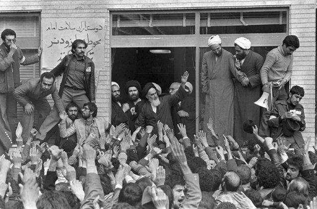 In this February 1, 1979 file photo, Ayatollah Ruhollah Khomeini, center, waves to followers as he appears on the balcony of his headquarters in Tehran, Iran. Forty years ago, Iran's ruling shah left his nation for the last time and an Islamic Revolution overthrew the vestiges of his caretaker government. The effects of the 1979 revolution, including the takeover of the U.S. Embassy in Tehran and ensuing hostage crisis, reverberate through decades of tense relations between Iran and America. (Photo by AP Photo/Campion/File)
