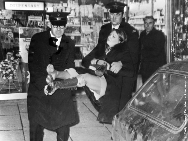 1971:  A young woman  injured during a shooting incident in Belfast is carried out of a chemist's shop by ambulance men