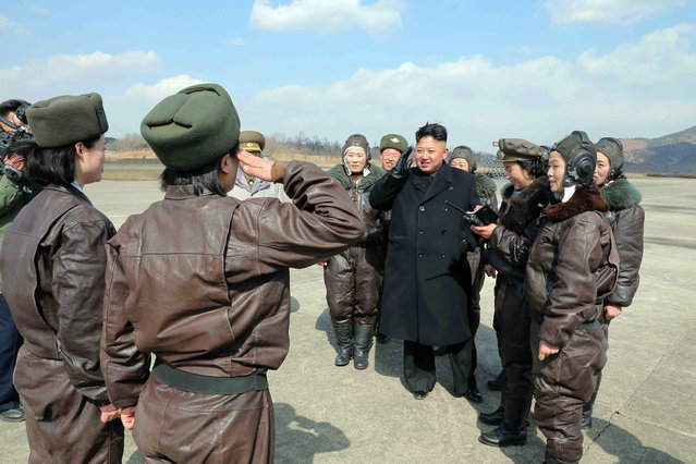 This undated picture released by North Korea's official Korean Central News Agency (KCNA) on March 7, 2014 shows North Korean leader Kim Jong-Un (4th R) saluting with female pilots as he inspects the Korean People's Army (KPA) Air and Anti-Air Force Unit 2620 honored with the Title of O Jung Hup-led 7th Regiment at an undisclosed location in North Korea. (Photo by AFP Photo/KCNA via KNS)