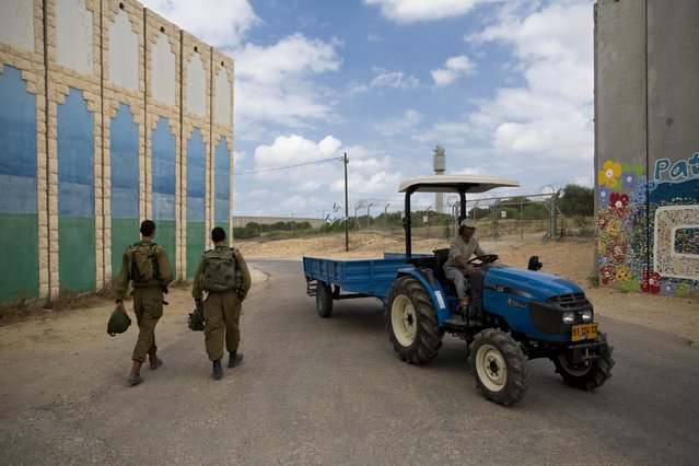 In this Thursday, June 25, 2015, photo, Israeli soldiers patrol as a farmer drives by, in Netiv Haasara near the Israel-Gaza border. (Photo by Oded Balilty/AP Photo)