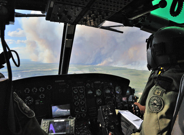 A handout photo provided by the Canadian Armed Forces on 06 May 2016 shows members from 408 Tactical Helicopter Squadron, Edmonton flying a CH-146 Griffon to view the damage created by wild fires in the Fort McMurray area, Alberta, Canada, 05 May 2016. The Canadian Armed Forces have air assets deployed in support of the Province of Alberta's wildfire emergency response efforts. (Photo by EPA/Canadian Armed)