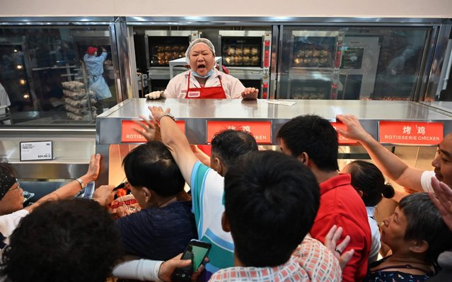 People try to get a roast chicken at the first Costco outlet in China, on the stores opening day in Shanghai on August 27, 2019. China has proved a brutal battleground for overseas food retailers in recent years, with many failing to understand consumer habits and tastes as well as local competitors building a stronger presence. (Photo by Hector Retamal/AFP Photo)
