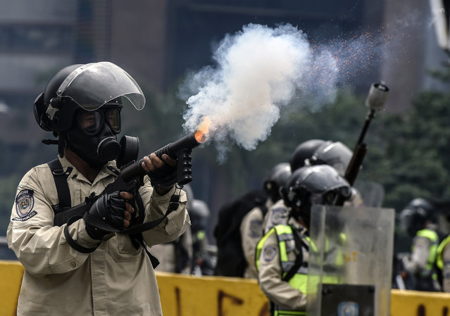 Riot police officers crack down on demonstrators during a protest against Venezuelan President Nicolas Maduro, in Caracas on April 20, 2017. (Photo by Juan Barreto/AFP Photo)