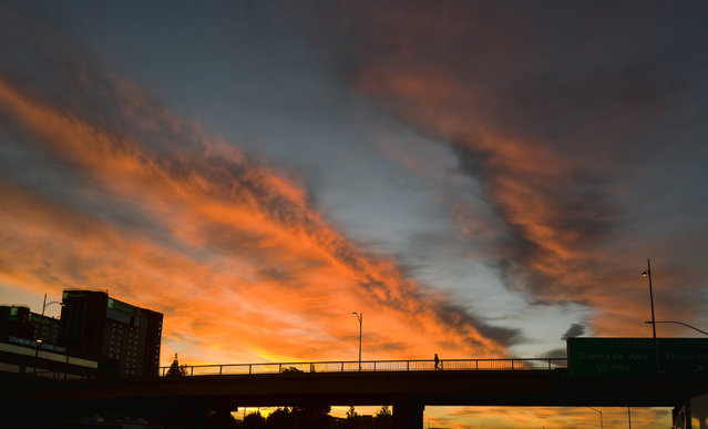 A pedestrian makes their way across an overpass under a dramatic sunrise during the early morning commute in Los Angeles on Friday, February 1, 2019. A powerful storm heading toward California is expected to produce heavy rainfall, damaging winds, localized stream flooding and heavy snow in the Sierra Nevada. Forecasters say rain will arrive in the north late Friday afternoon and reach the south late in the night, and last through Saturday night. (Photo by Richard Vogel/AP Photo)