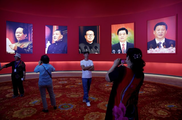 A visitor poses in front of pictures of late Chinese Chairman Mao Zedong, former Chinese leaders Deng Xiaoping, Jiang Zemin, Hu Jintao and Chinese President Xi Jinping during an exhibition on China's achievements to mark the 70th anniversary of the founding of the People's Republic of China at the Beijing Exhibition Center, September 24, 2019. (Photo by Jason Lee/Reuters)