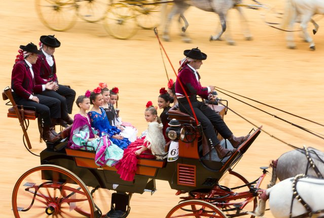 """Spanish carriage drivers from Andalusia perform in the bullring, or """"La Real Maestranza"""", in Seville during the carriage competition held within the Feria de Abril (April Fair), in Seville, Spain, 30 April 2017. Carriages from a single horse to five horses took part in a parade through town and then during manoeuvres inside the bullring. (Photo by Jim Hollander/EPA)"""