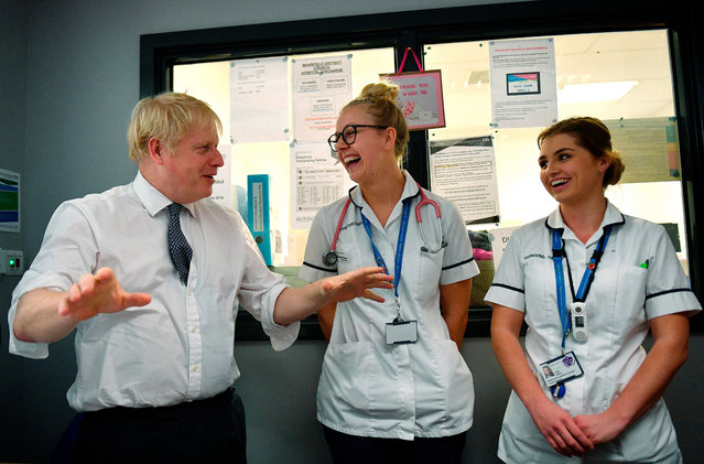 Britain's Prime Minister Boris Johnson talks with staff at King's Mill Hospital in Mansfield, northern England, Friday November 8, 2019, during a general election campaign visit.  Britain goes to the polls on Dec. 12 to vote in a pre-Christmas general election. (Photo by Daniel Leal-Olivas/Pool via AP Photo)