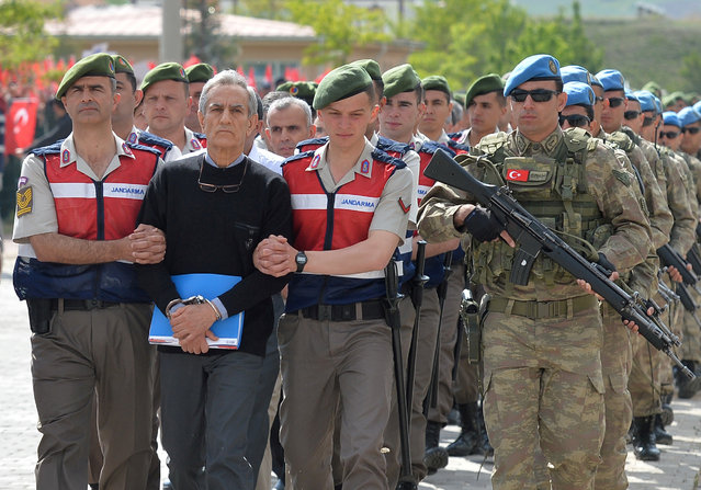 Akin Ozturk, a former Turkish Air Force commander who is accused of plotting and orchestrating last year's failed coup, is escorted by gendarmes as he arrives at the court in Ankara, Turkey, May 22, 2017. (Photo by Reuters/Stringer)