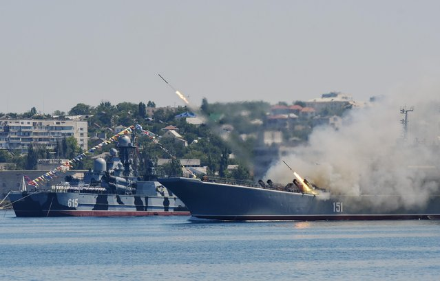 Missiles are fired by a Russian navy battle ship during a rehearsal of the Russian Navy Day parade in Sevastopol, Crimea, Friday, July 24, 2015. (Photo by Alexander Polegenko/AP Photo)