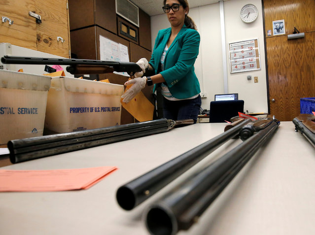 "A woman inventories a shotgun that was turned in from the public as part of the ""Gun Turn-in"" event where a gift card is given for every firearm turned over to the Chicago Police in Chicago, Illinois, U.S. May 28, 2016. (Photo by Jim Young/Reuters)"