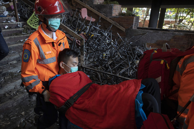 A man is evacuated by medics past charred debris from the Polytechnic University in Hong Kong on Wednesday, November 20, 2019. Hong Kong schools have reopened after a six-day shutdown but students were facing transit disruptions as the last protesters remained holed up on a university campus. (Photo by Ng Han Guan/AP Photo)