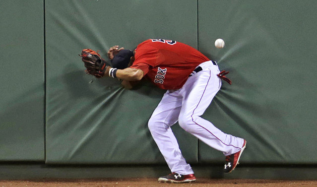 Boston Red Sox center fielder Mookie Betts hits the wall after losing track of the ball on a triple by Detroit Tigers' Ian Kinsler during the eighth inning of a baseball game at Fenway Park in Boston, Friday, July 24, 2015. (Photo by Charles Krupa/AP Photo)