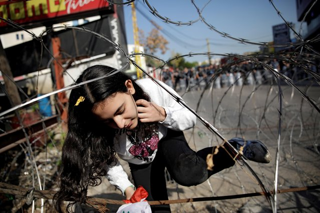 A girl walks among a barbed wire blocking the road to the U.S. Embassy during a protest in Awkar, Lebanon on November 24, 2019. (Photo by Andres Martinez Casares/Reuters)