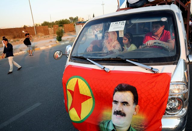 In this Saturday, July 25, 2015 photo, Kurdistan Workers' Party, or PKK, supporters drive past a demonstration against the Turkish government, in Irbil, the Northern Kurdish region of Iraq. The image of Kurdish guerrilla leader Abdullah Ocalan on a flag is hung on the front of the vehicle. (Photo by Bram Janssen/AP Photo)