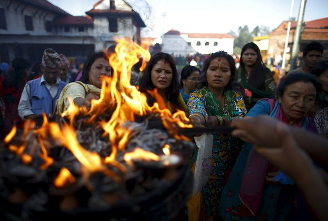 Devotees offer lamps while offering prayers at Pashupatinath temple to mark the Shrawan Sombar festival in Kathmandu July 27, 2015. (Photo by Navesh Chitrakar/Reuters)