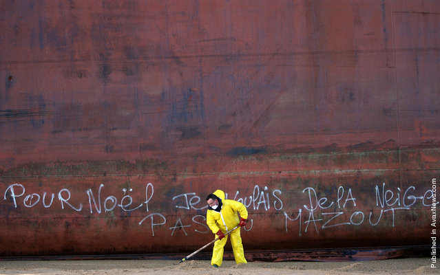 """A French civil guard clears sand contaminated with fuel oil on Kerminihy beach after the TK Bremen cargo ship was stranded by high winds, on December 17, 2011. Graffiti on the side of the ship reads in French: """"For Christmas, I wanted some snow, not fuel oil"""""""