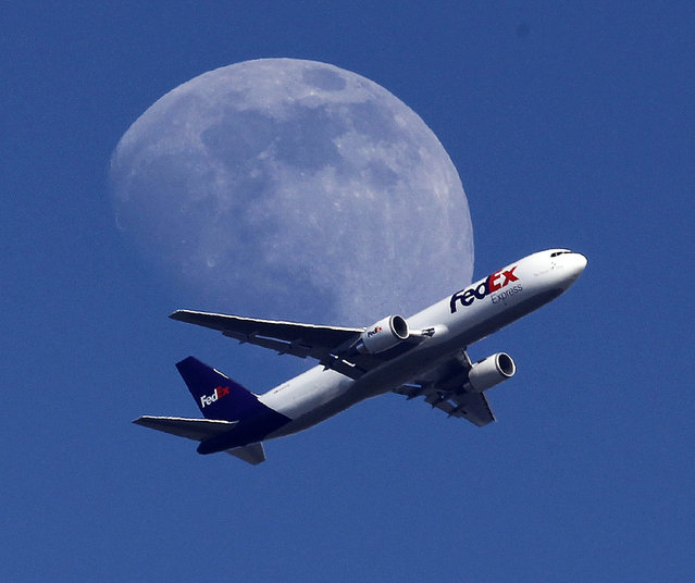 A Fed Ex cargo airplane passes over Whittier, Calif., on its way to Los Angeles International Airport, Sunday, July 26, 2015. (Photo by Nick Ut/AP Photo)
