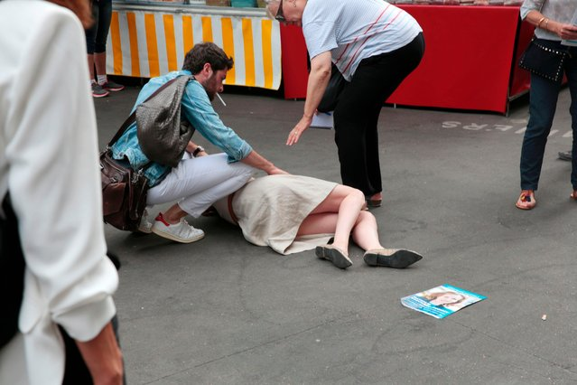 Bystanders gives assistance after Les Republicains (LR) party candidate Nathalie Kosciusko- Morizet collapsed while campaigning in the 5th arrondissement in Paris on June 15, 2017, ahead of the second round of the French legislative election. (Photo by Geoffroy Van Der Hasselt/AFP Photo)