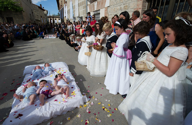 Girls throw confetti on babies during el Salto del Colacho (the devil's jump) festival on June 22, 2014 in Castrillo de Murcia, Spain. The festival, held on the first Sunday after Corpus Cristi, is a catholic rite of the devil cleansing babies of original sin by jumping over them. (Photo by Denis Doyle/Getty Images)